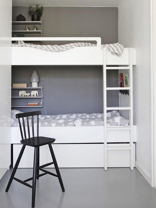 Habitación compartida con litera y predominio del blanco.